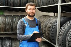 有剪贴板的推销员在轮胎附近 库存照片