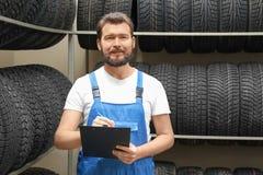 有剪贴板的推销员在轮胎附近 免版税库存图片