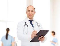 有剪贴板和听诊器的微笑的男性医生 图库摄影