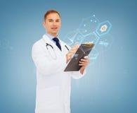 有剪贴板和听诊器的微笑的男性医生 免版税库存照片