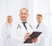 有剪贴板和听诊器的微笑的男性医生 免版税库存图片