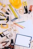 有剪贴板和图纸的不同的工具在木桌面 库存照片