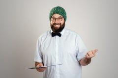 有剪贴板和绿色盖帽的有胡子的人 库存图片