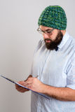 有剪贴板和绿色盖帽的有胡子的人 免版税库存图片