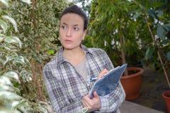 有剪贴板控制植物的妇女在园艺中心 库存照片