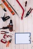 有剪贴板的不同的工具在与拷贝空间的木桌面 库存照片