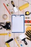 有剪贴板的不同的工具在木桌面 免版税库存图片