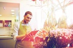 有剪贴板的卖花人人在花店 免版税库存图片