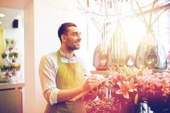 有剪贴板的卖花人人在花店 图库摄影