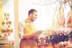 有剪贴板的卖花人人在花店 库存照片