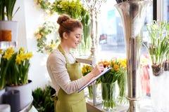 有剪贴板的卖花人妇女在花店 免版税库存图片