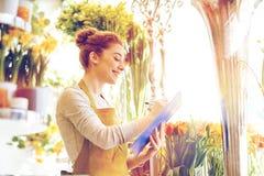 有剪贴板的卖花人妇女在花店 免版税图库摄影