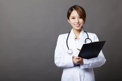 有剪贴板的微笑的女性医生 免版税库存图片