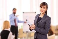 有剪贴板的微笑的妇女在办公室 库存照片