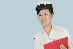 有剪贴板的愉快的女性美国海军官员微笑在浅兰的背景的 免版税库存照片
