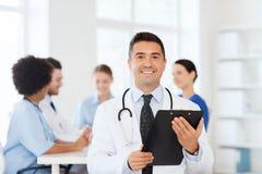 有剪贴板的愉快的医生在医疗队 库存照片
