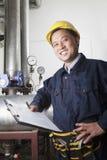 有剪贴板的检查输油管设备的微笑的工作者画象在天然气加工厂,北京,中国 免版税库存照片