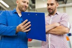 有剪贴板的汽车的汽车机械师和人购物 免版税库存照片