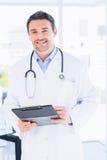 有剪贴板的确信的男性医生在医院 免版税库存图片