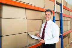 有剪贴板的经理在配给物仓库里 库存图片