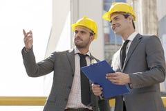有剪贴板的年轻男性建筑师谈论在建造场所 库存图片