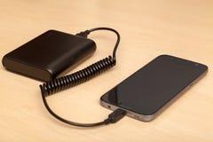 有力量银行的充电的智能手机 免版税图库摄影