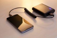 有力量银行的充电的智能手机 库存照片