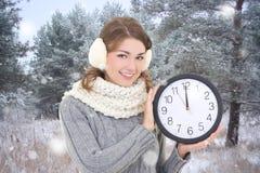 有办公室时钟的美丽的妇女在冬天森林里 图库摄影