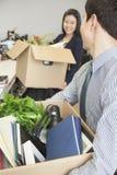 有办公室项目的两个年轻商人运载的箱子 免版税图库摄影
