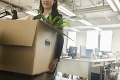 年轻有办公用品的女实业家移动的箱子 库存图片
