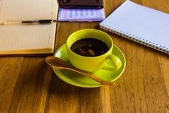有办公用品的绿色咖啡杯 库存图片