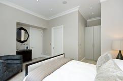 有加长型的床的当代卧室与豪华家具 免版税库存照片