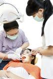 有助手和患者的亚裔牙科医生 库存照片