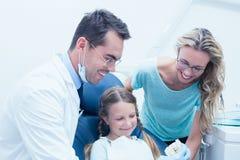 有助理和女孩的愉快的男性牙医 免版税图库摄影