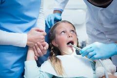 有助理审查的女孩牙的牙医 免版税库存图片