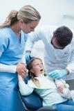 有助理审查的女孩牙的牙医 库存照片