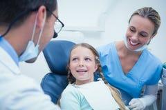 有助理审查的女孩牙的牙医 免版税库存照片