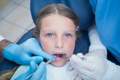 有助理审查的女孩牙的牙医 免版税图库摄影