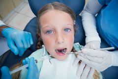 有助理审查的女孩牙的牙医 图库摄影