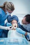 有助理审查的女孩牙的牙医 库存图片