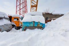 有勾子的流动建筑用起重机和有些卡车在随风飘飞的雪 免版税库存照片