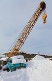 有勾子的老流动建筑用起重机在随风飘飞的雪 免版税库存照片