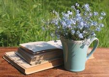 有勿忘草和书花束的水罐在木桌上 免版税库存照片