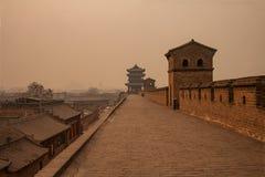 有包围古城平遥的塔的每老的墙壁 在与来自与co的热化的烟雾的一有雾的天射击的图象 库存图片