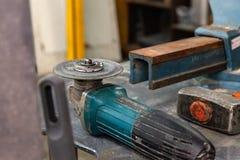 有包括一把大重的绑制钳、角度研磨机、螺丝刀、切削刀、大锤和备用的一套的工作凳工具 免版税库存照片