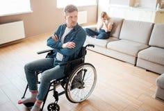 有包括的年轻人和伤残坐在前面的轮椅 手横渡了并且弄翻了 年轻女人坐后边 免版税库存照片