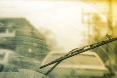 有包括的玻璃清洁剂的肮脏的汽车挡风玻璃,在背景的大城市前面和后面被弄脏 免版税库存图片