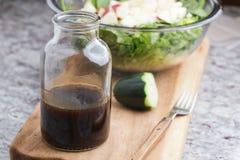 有包括香醋、蜂蜜和橄榄油的色拉调味品的一个玻璃瓶 库存照片