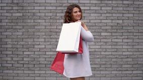 有包裹的一个女孩在购物以一种好心情以后对石头墙壁  慢的行动 股票录像