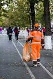 有包裹的一名妇女清洗街道残骸俄罗斯,克拉斯诺达尔, 10月7,2018 图库摄影